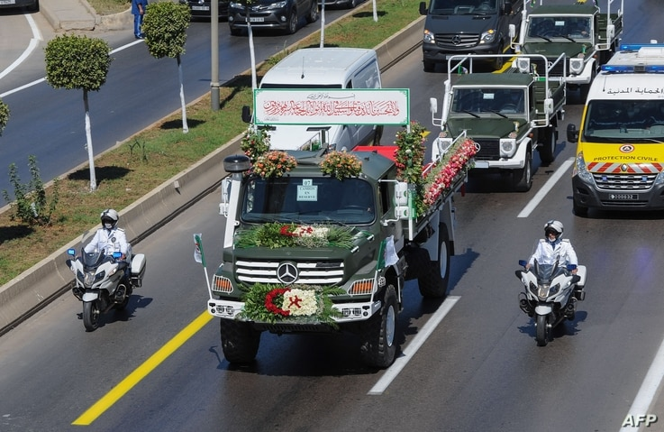 A convoy of coffins draped with the national flag containing the remains of 24 Algerian resistance fighters killed during the…