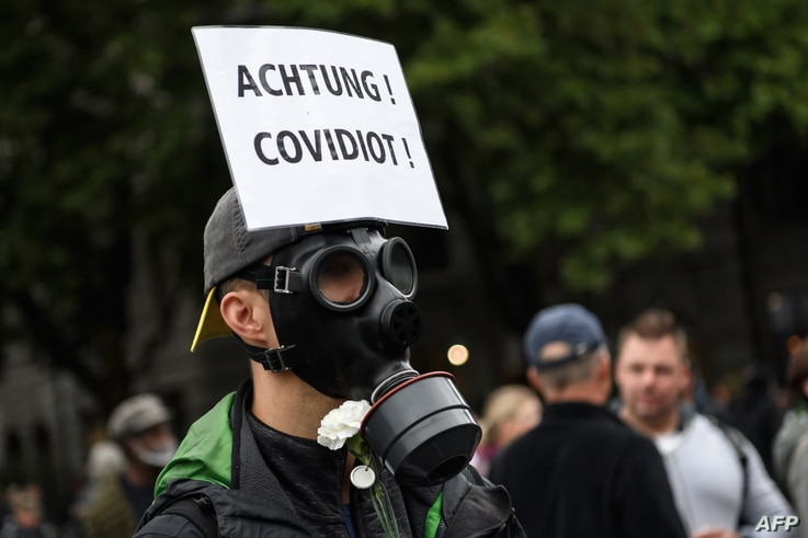 """A man with a placard reading in Gamany: """" Watch out! Covidiot"""" takes part to a protest against the increasing requirements in…"""