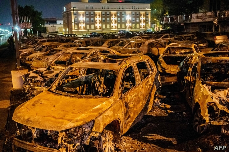 TOPSHOT - The carcasses of the cars burned by protestors the previous night during a demonstration against the shooting of…
