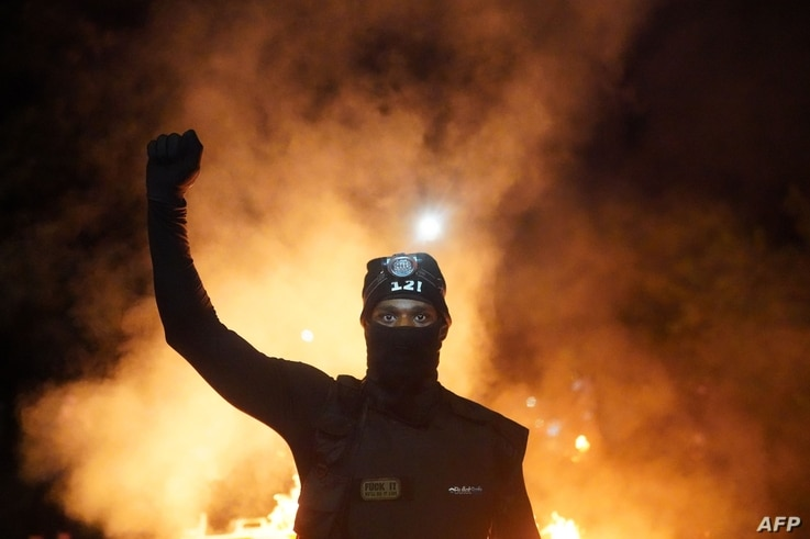 PORTLAND, OR - AUGUST 23: A protester holds his fist in the air during a protest against racial injustice and police brutality…
