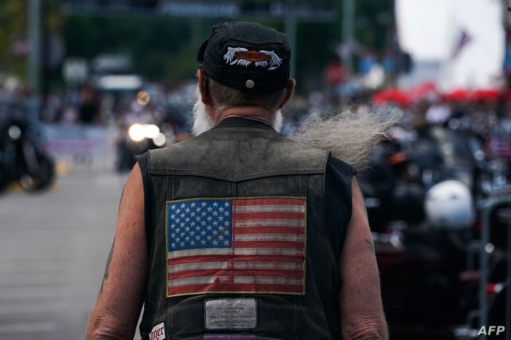 A man with a long beard wears a vest with the US flag on the back as he walks on Main Street during the 80th Annual Sturgis…