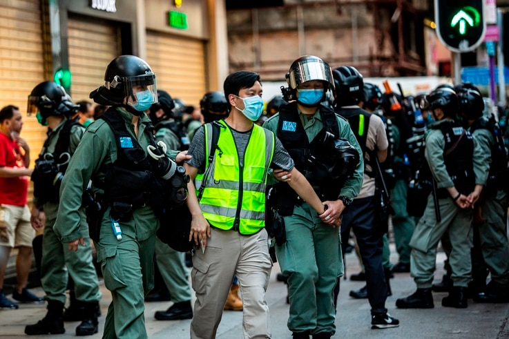 (FILES) In this file photo police arrest a man (C) and lead him to a nearby bus during a protest against China's planned…