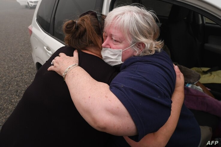 Margi Wyatt (R) is comforted by mobile home park manager Valerie after Wyatt returned to the R.V. park to find her home…