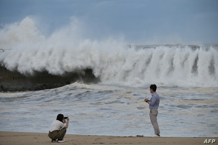 TOPSHOT - A couple take photos along a sea wall of the waves brought by Typhoon Haishen in the eastern port city of Sokcho on…