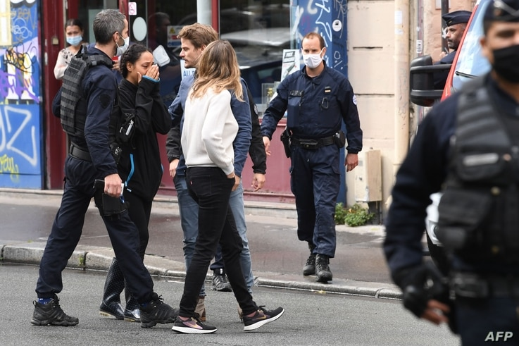A woman reacts after several people were injured near the former offices of the French satirical magazine Charlie Hebdo…