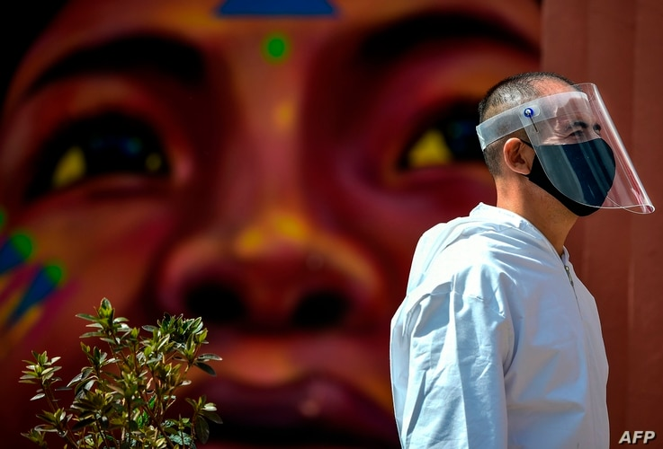 A man wears a face mask and shield in the Chorro de Quevedo tourist area in Bogota on September 3, 2020 amid the COVID-19 novel…