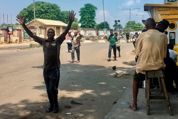 TOPSHOT - People are obliged to walk with their hands upon their heads as they pass security checkpoints, held by security…