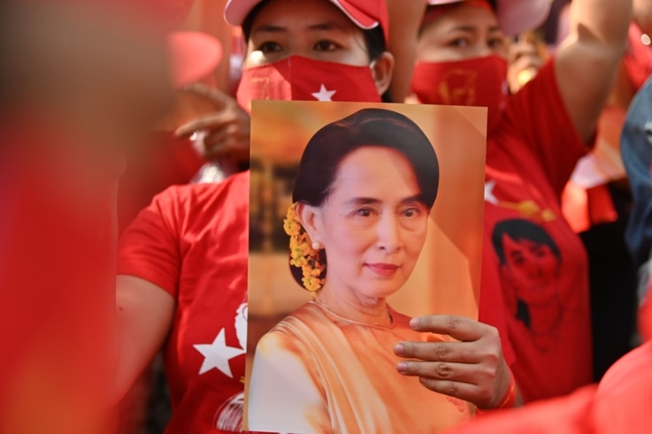 A Myanmar migrant holds up an image of Aung San Suu Kyi during a demonstration outside the Myanmar embassy in Bangkok on…