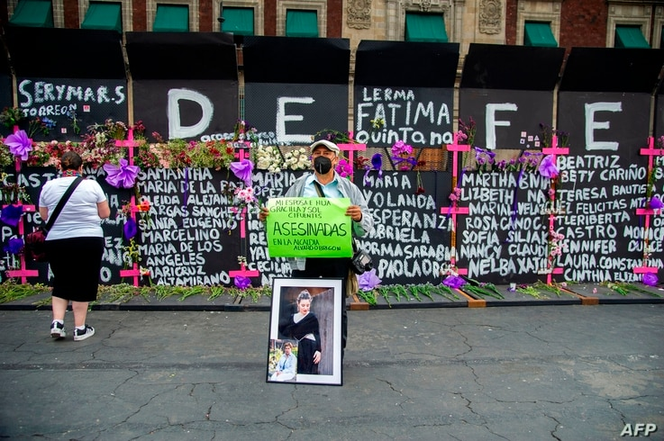 A man holds a sign and the portrait of a victim of femicide in front of a metal fence with the names of other victims…