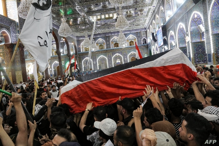 Mourners carry the body of Iraqi anti-government activist Ihab al-Wazni (Ehab al-Ouazni) during his funeral at the Imam Hussein…