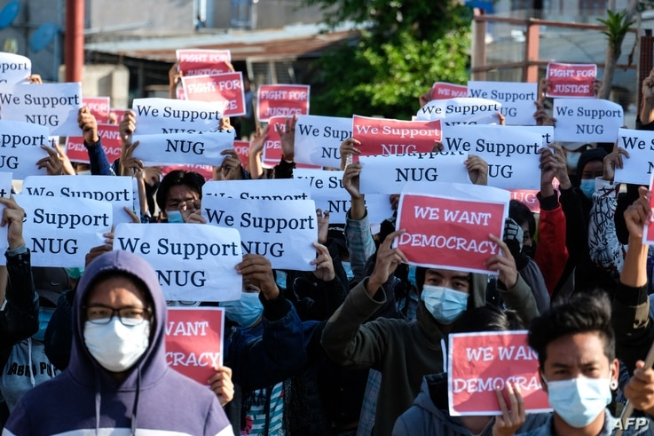 Protesters hold posters in support of the National Unity Government (NUG) during a demonstration against the military coup on …