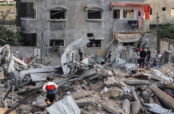 Palestinians check the damage amid the rubble of a destroyed building on the first day of the Eid al-Fitr holiday, which marks...