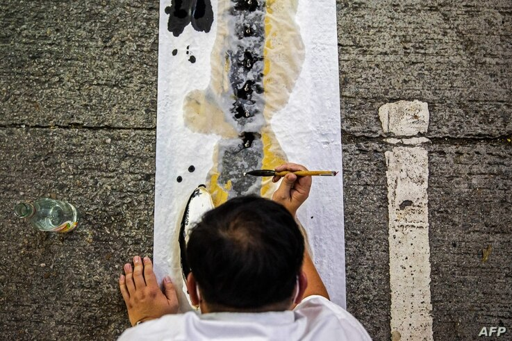An artist takes part in a performance art in the Causeway Bay district of Hong Kong on June 3, 2021, to mourn the victims of…