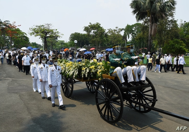 Philippine military officers (white) and honor guards together with family members march alongside the carriage carrying the...