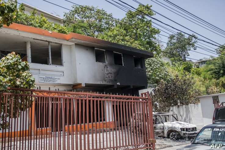 A charred car and building are pictured near the Petionville Police station after incidents, where suspects of being involved…