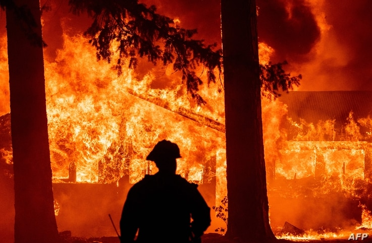 Firefighters attempt to get control of the scene as dozens of homes burn during the Dixie in the Indian Falls neighborhood of...