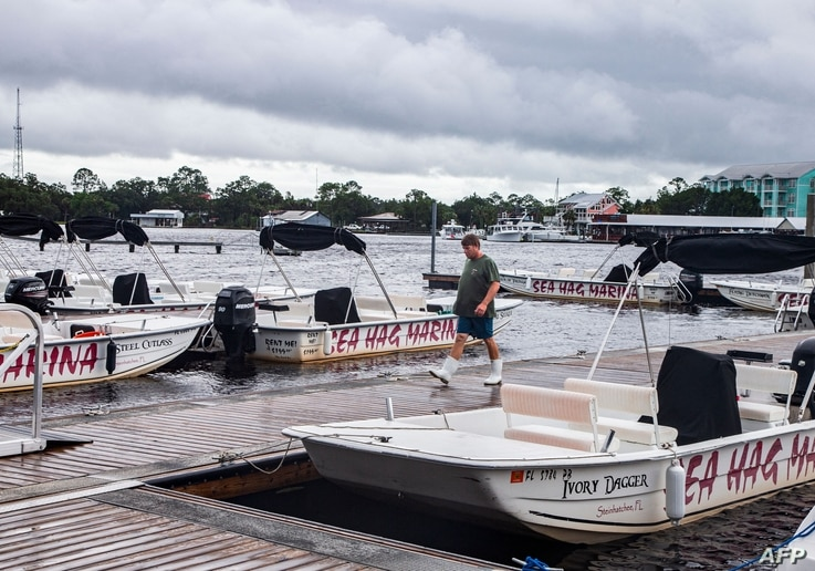 STEINHATCHEE, FL - JULY 07: Kyle Raison walks along the dock at the Sea Hag Marina as scallop rental boats are tied off after...