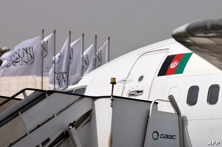 An aircraft with Afghanistan's flag is seen in front of Taliban flags fluttering on poles at the airport in Kabul on September...