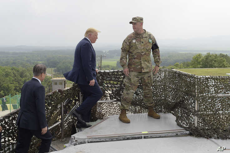 President Donald Trump and South Korean President Moon Jae-in, left, walk up to view North Korea from the Korean Demilitarized Zone from Observation Post Ouellette at Camp Bonifas in South Korea, Sunday, June 30, 2019.