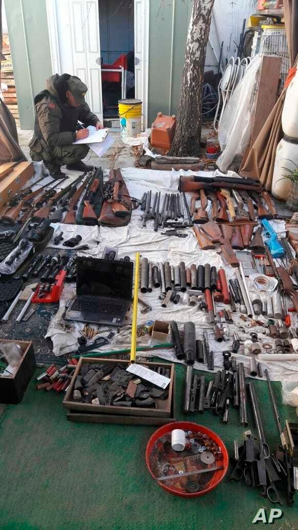 In this photo provided by the Argentine Ministry of Security, a police officer takes inventory a cachet of weapons seized by authorities at an undisclosed location in Argentina, Wednesday, June 26, 2019. Authorities seized about 1,000 guns and…