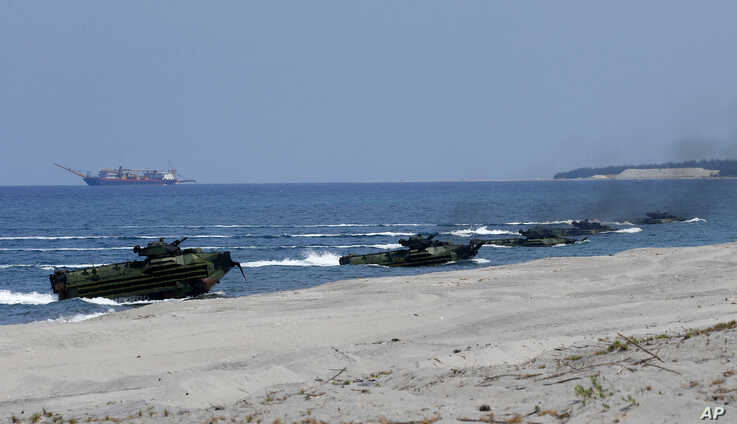 """Amphibious Assault Vehicles carrying U.S. and Philippine troops, make a beach landing during the Joint US-Philippine Military Exercise dubbed """"Balikatan 2019"""" April 11, 2019, off San Antonio, Zambales province northwest of Manila, Philippines."""