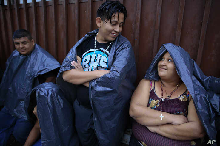 Migrants from El Salvador talk as they wait in the rain outside the Mexican Commission for Refugee Assistance office where hundreds a day line up to seek a document permitting them to legally be in the country in Tapachula, Mexico, June 13, 2019.
