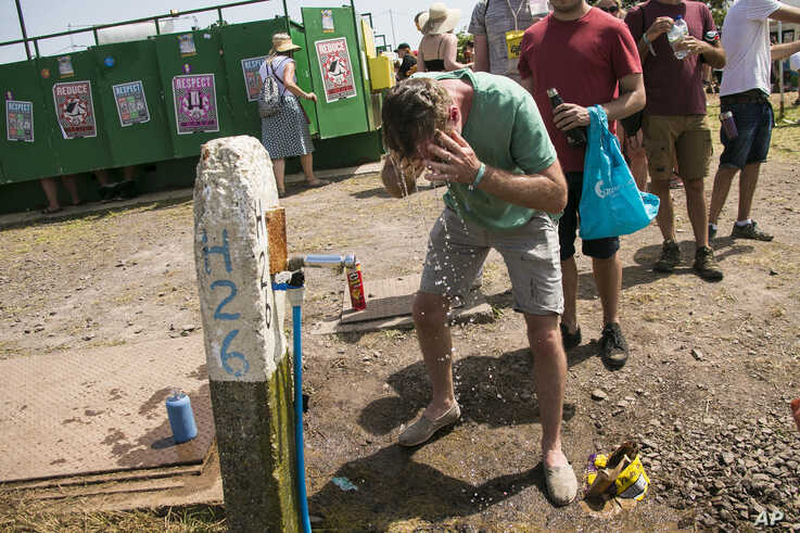 A festival goers pours water on his head at a water station, on the third day of Glastonbury Festival at Worthy Farm, Somerset, England, Friday, June 28, 2019. Temperatures are expected to soar over the weekend as a heatwave hits parts of Europe,…
