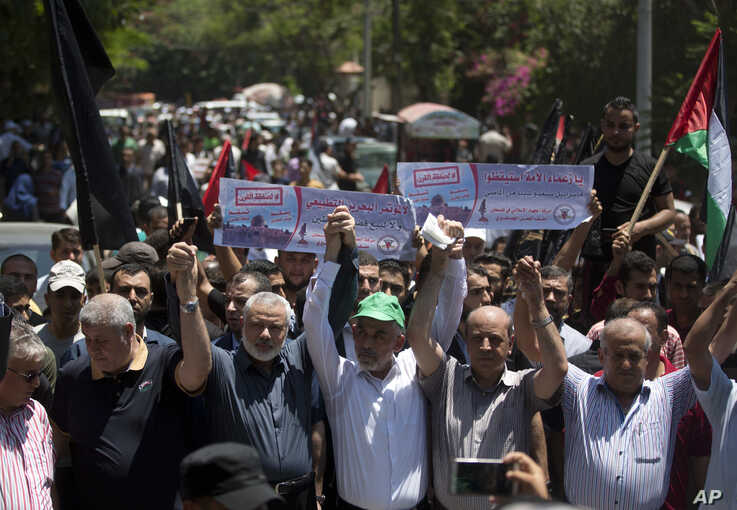 Head of the Hamas political bureau, Ismail Haniyeh, third from left, and Hamas leader in the Gaza Strip Yahya Sinwar raise their hands up with leaders of the other Palestinian factions as they attend a protest against the conference in Bahrain,…