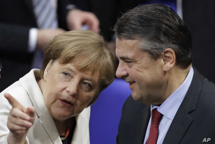 German Chancellor Angela Merkel, left, talks to outgoing Foreign Minister Sigmar Gabriel when Germany's parliament Bundestag meets to elect Angela Merkel for a fourth term as chancellor in Berlin, Germany, Wednesday, March 14, 2018.