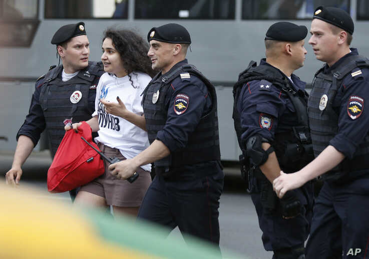 Police officers detain a supporter of Russian investigative journalist Ivan Golunov during a march in Moscow, Russia, June 12, 2019.