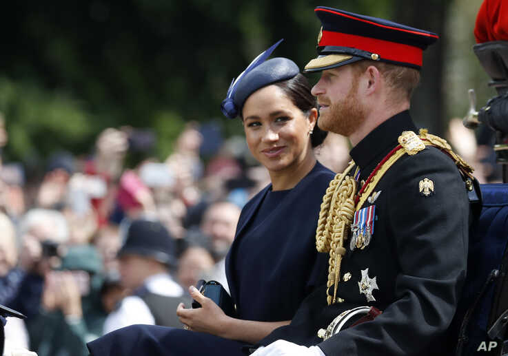 FILE - Britain's Meghan, the Duchess of Sussex and Prince Harry ride in a carriage to attend the annual Trooping the Colour Ceremony in London, June 8, 2019.