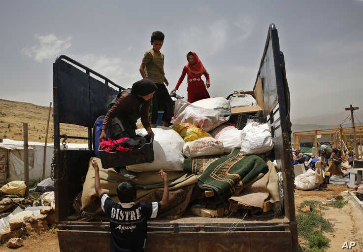 A Syrian family loads their belongings on a pickup, as they evacuate an informal refugee camp after a fight broke out last week between camp residents and Lebanese firefighters who arrived to put out a fire, in Deir Al-Ahmar, east Lebanon, Sunday,…