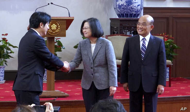 In this image made from video, Taiwan's outgoing Premier Lai Ching-te, left, shakes hands with President Tsai Ing-wen, center, as newly appointed Premier Su Tseng-chang, right, looks on after a press conference at the presidential office in Taipei, Taiwan, Jan. 11, 2019.
