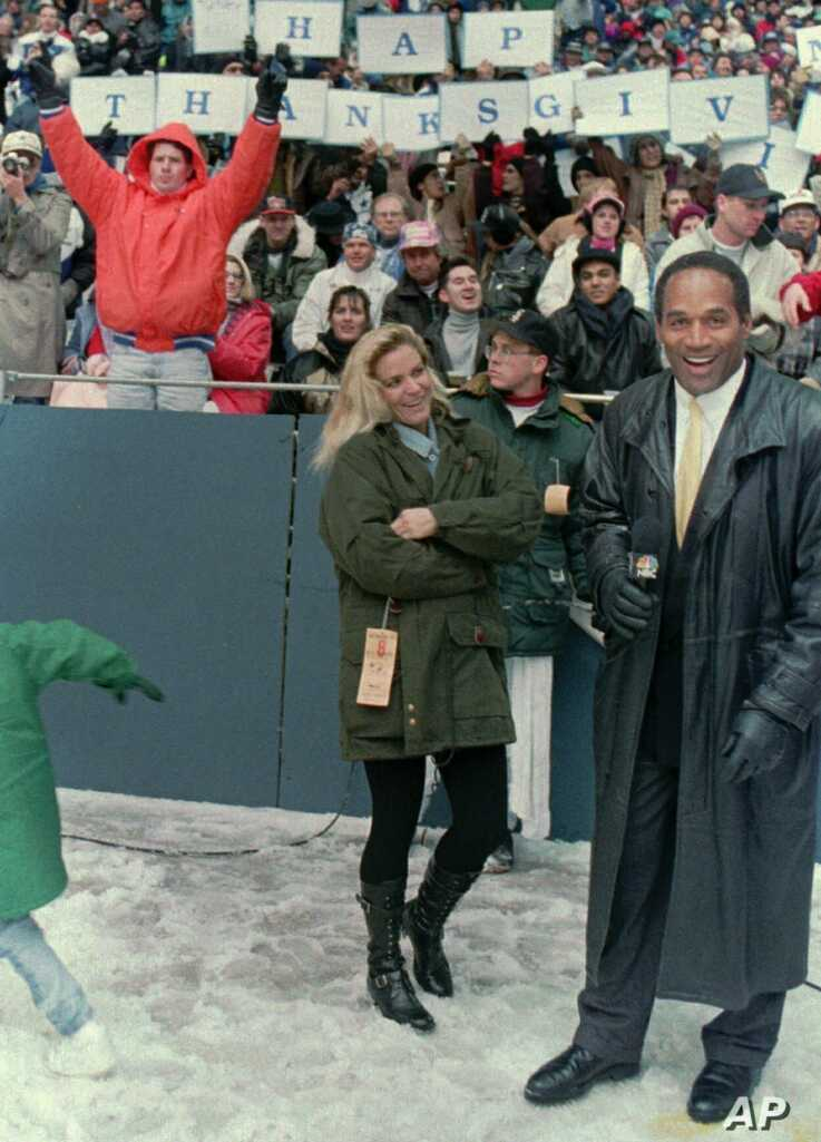 FILE - O.J. Simpson stands with Nicole Brown Simpson while broadcasting on the sidelines during the Thanksgiving Day NFL football game in Irving, Texas, Nov. 25, 1993.