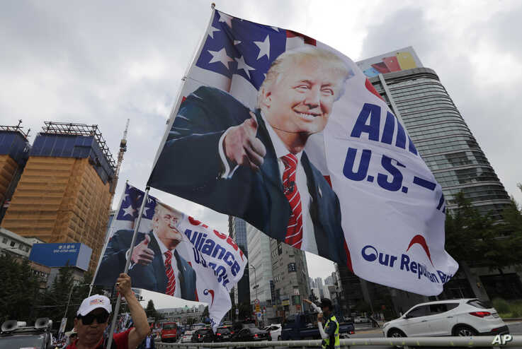 South Korean conservative activists hold huge flags with pictures of U.S. President Donald Trump as they march after a rally to welcome a planned his visit in Seoul, South Korea, Saturday, June 29, 2019. North Korea said Saturday President Donald…