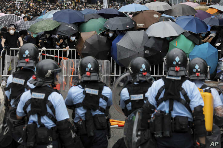 Policemen in anti-riot gear stand watch as protesters use umbrellas to shield themselves near the Legislative Council in Hong Kong, June 12, 2019.