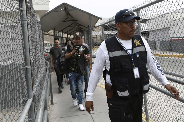 A security guard leads a group of U.S. asylum-seekers out of Mexican immigration offices after they were returned by U.S. authorities to wait in Mexico under the so-called Remain in Mexico program, in Ciudad Juarez, Mexico, Wednesday, July 17, 2019…