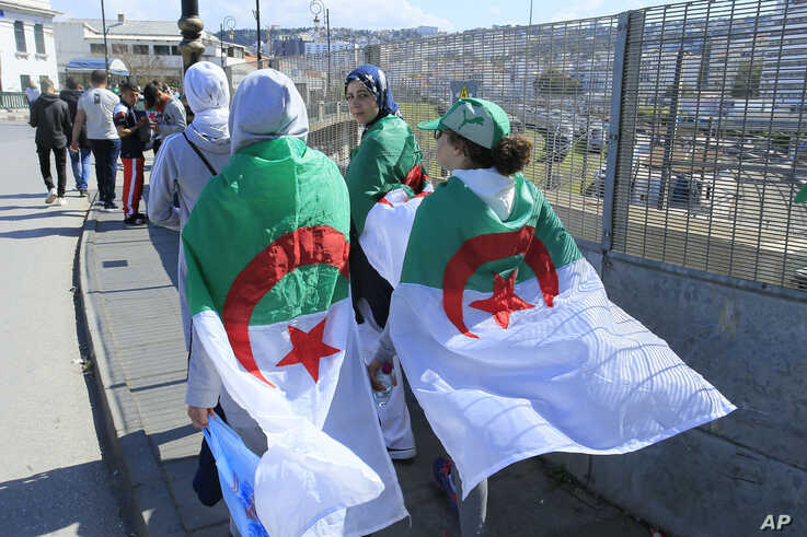 Women wear the Algerian flag during a protest in Algiers, Friday, April 26, 2019. Algerians are massing for a 10th week of protests against their country's ruling class, calling for the ex-president's brother to be put on trial. (AP Photo/Anis…