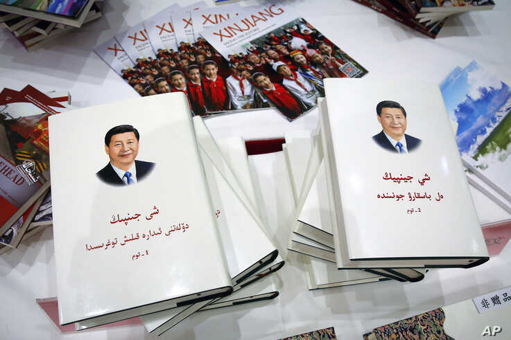 Copies of the book on the governance of Chinese President Xi Jinping are displayed with booklets promoting Xinjiang during a press conference by Shohrat Zakir, chairman of China's Xinjiang Uighur Autonomous Region, in Beijing, July 30, 2019.