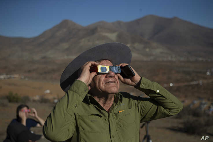 A man looks up at a total solar eclipse in La Higuera, Chile, Tuesday, July 2, 2019. Northern Chile is known for clear skies and some of the largest, most powerful telescopes on Earth are being built in the area, turning the South American country…
