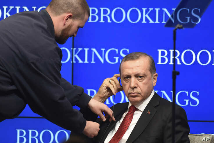 Turkish President Recep Tayyip Ergodan is fitted with an earpiece during an event at the Brookings Institution in Washington,Thursday, March  31, 2016. (AP Photo/Kevin Wolf)