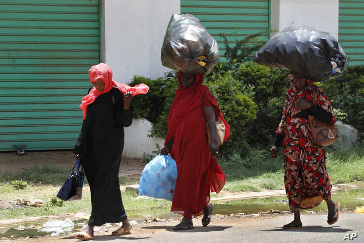 """Sudanese women carry on their heads big bags of empty plastic bottles, as they walk on the street, in Khartoum, Sudan, Saturday, June 15, 2019. The top U.S. diplomat to Africa says there needs to be an """"independent and credible"""" investigation into…"""