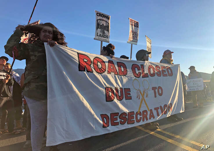 Demonstrators gather to block a road at the base of Hawaii's tallest mountain, Monday, July 15, 2019, in Mauna Kea, Hawaii, to protest the construction of a giant telescope on land that some Native Hawaiians consider sacred.