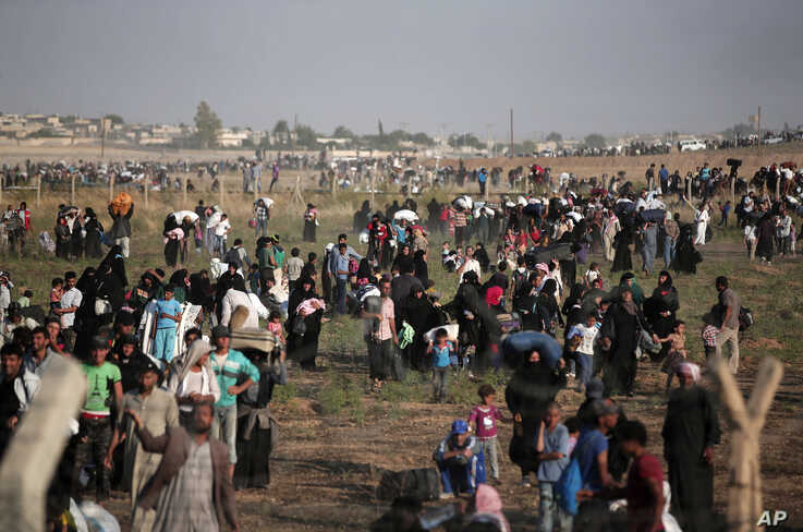 FILE - In this June 14, 2015 file photo taken from the Turkish side of the border between Turkey and Syria, in Akcakale, Sanliurfa province, southeastern Turkey, thousands of Syrian refugees walk in order to cross into Turkey. Turkey has been…