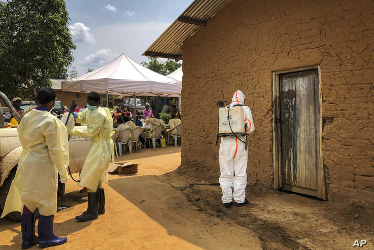 A worker from the World Health Organization (WHO) decontaminates the doorway of a house on a plot where two cases of Ebola were found, in the village of Mabalako, in eastern Congo Monday, June 17, 2019. Health officials in eastern Congo have begun…