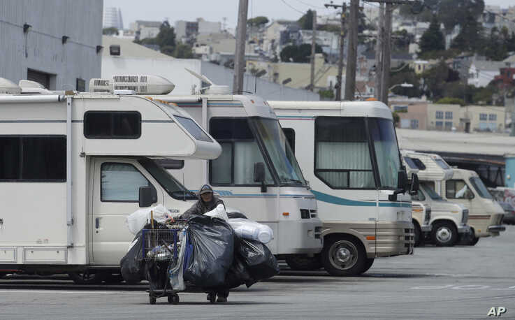FILE - A homeless person pushes a cart past parked RVs along a street in San Francisco, California, June 27, 2019.