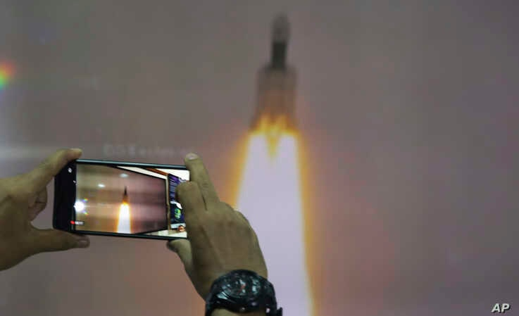 A man at New Delhi's Nehru Planetarium, takes pictures of a web cast of the lift off of Indian Space Research Organization (ISRO)'s Geosynchronous Satellite launch Vehicle (GSLV) MkIII carrying Chandrayaan-2 from Satish Dhawan Space center, July 22, 2019.