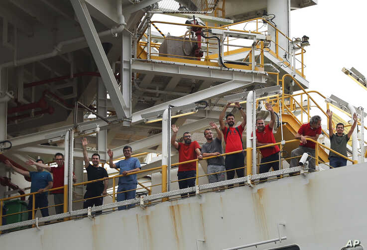Crew members of Turkey's 230-meter (750-foot) drillship 'Yavuz' wave as the ship leaves the port of Dilovasi, outside Istanbul, on its way to the Mediterranean, Thursday, June 20, 2019. Turkey has launched Yavuz, a second drillship that will drill…