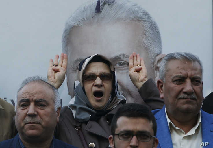 Backdropped by a poster of Binali Yildirim, former Prime Minister and candidate for Istanbul of the ruling Justice and Development Party's (AKP), people chant Islamic slogans during a protest in Istanbul, Monday, March 11, 2019. The crowd…