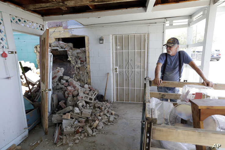 Eugene Johnson, right, looks at the chimney collapsed by an earthquake, July 6, 2019, at his home in Trona, Calif.